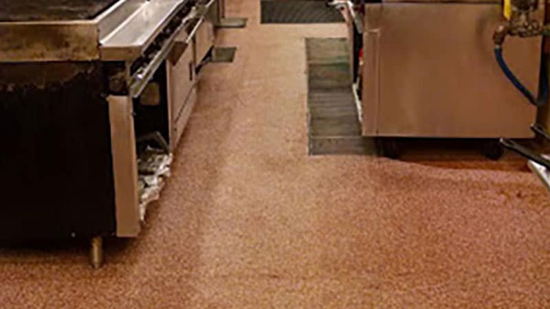 An up-close photo of the red epoxy floor of a hotel kitchen