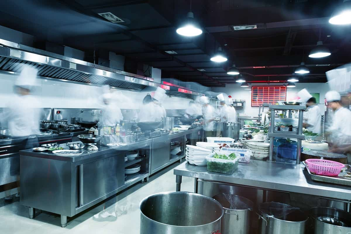 Cooks are busily working in a commercial restaurant kitchen